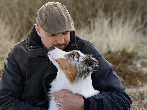The Importance of Dog Behavior Training with Australian Shepherds - Photo: Man hugging Australian Shepherd outdoors.