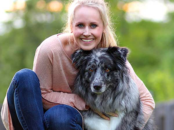 Blonde lady hugging her blue merle Australian Shepherd outdoors.