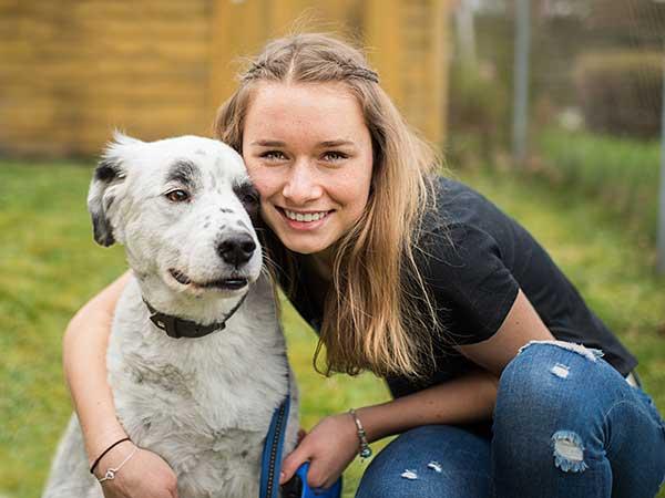 Young woman hugging Australian Shepherd.