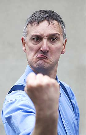 Mature man in blue shirt shaking fist.