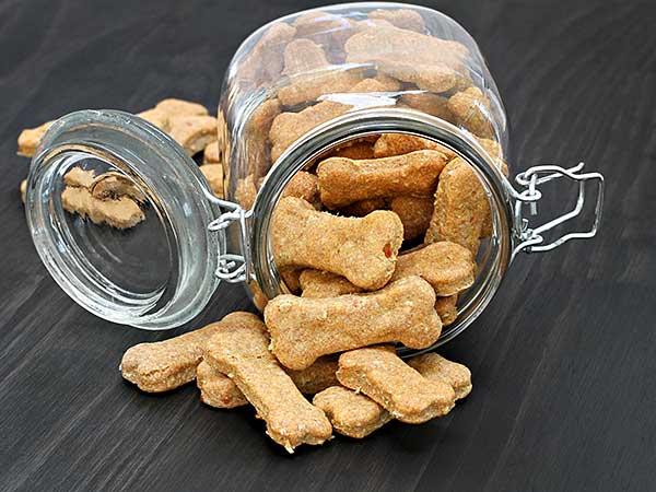 Homemade dog treats spilling from a glass jar.